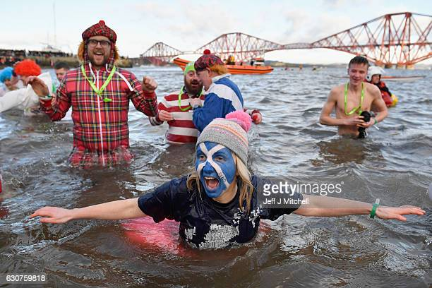 Members of the public wearing fancy dress in the the water as they join around 1000 New Year swimmers many in costume in front of the Forth Rail...