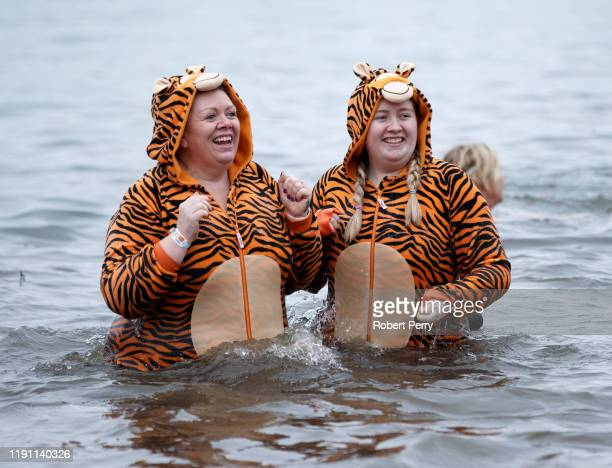 Members of the public wearing fancy dress react to the water as they join New Year swimmers many in costume in front of the Forth Rail Bridge during...