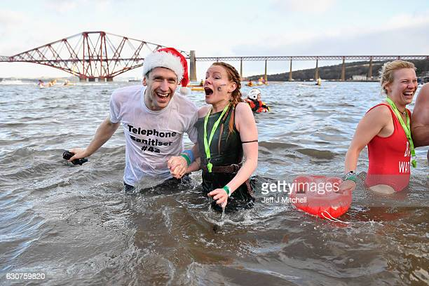 Members of the public wearing fancy dress react to the water as they join around 1000 New Year swimmers many in costume in front of the Forth Rail...