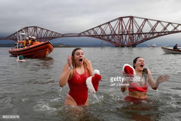 Members of the public wearing fancy dress react to the water as they join around 1100 New Year swimmers many in costume in front of the Forth Rail...