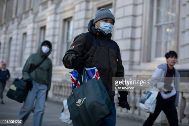 Members of the public wearing masks walk down Whitehall on March 12, 2020 in London, England. The FTSE 100 Index fell 5054 per cent when trading...