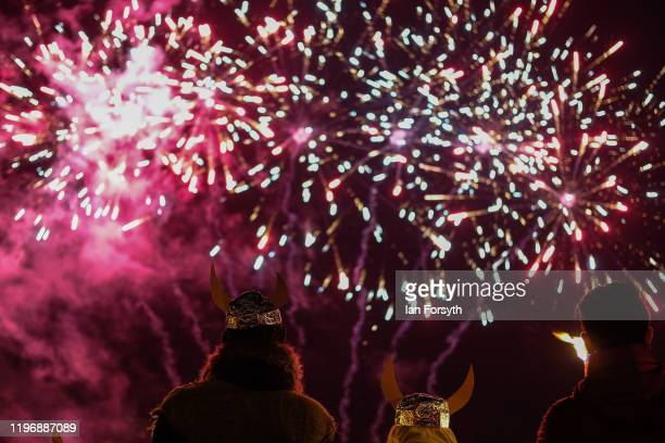 Members of the public wearing Viking helmets watch as fireworks explode overhead during New Year's Eve celebrations at the Flamborough Fire Festival...