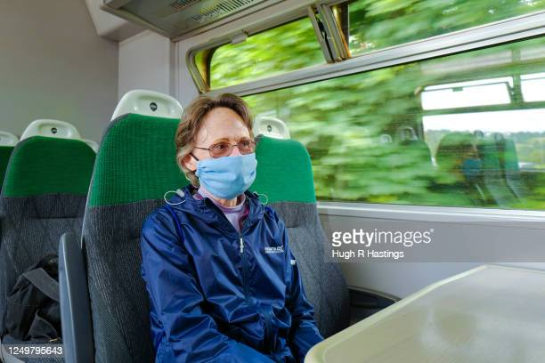 Members of the public wears a face mask while travelling on the Truro to Falmouth Town GWR branch line on June 15, 2020 in Truro, Cornwall. The...