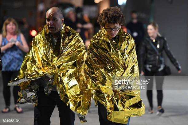 Members of the public wrapped in emergency blankets leave the scene of a terror attack on London Bridge in central London on June 3 2017 Armed police...