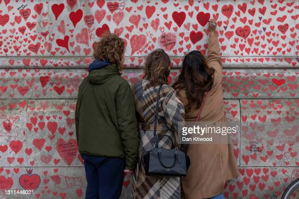 Members of the public write on a covid memorial wall on April 08, 2021 in London, England. The Covid-19 Bereaved Families for Justice group said of...