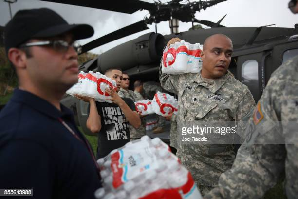 Members of the Puerto Rican National Guard deliver food and water via helicopter to hurricane survivors as they deal with the aftermath of Hurricane...