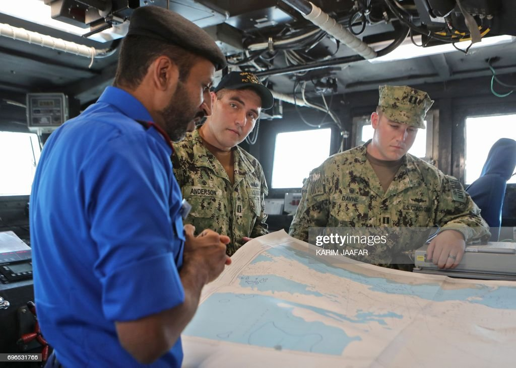 members of the qatari navy l and the us navy are seen looking at a map inside a vessel during a joint military exercise between qatar and the us navy