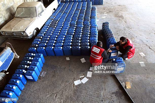 Members of the Qatari Red Crescent prepare aid in the form of diesel fuel to deliver to families in need in the rebelheld town of Beit Sawa on the...