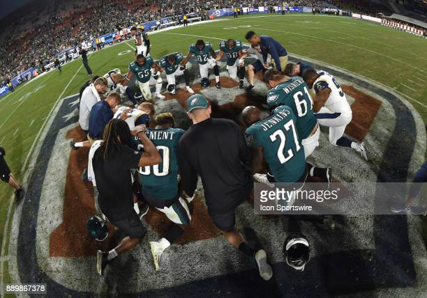 Members of the Rams and Eagles take a knee at the 50 yard line to say a prayer at the conclusion of the game during an NFL game between the...