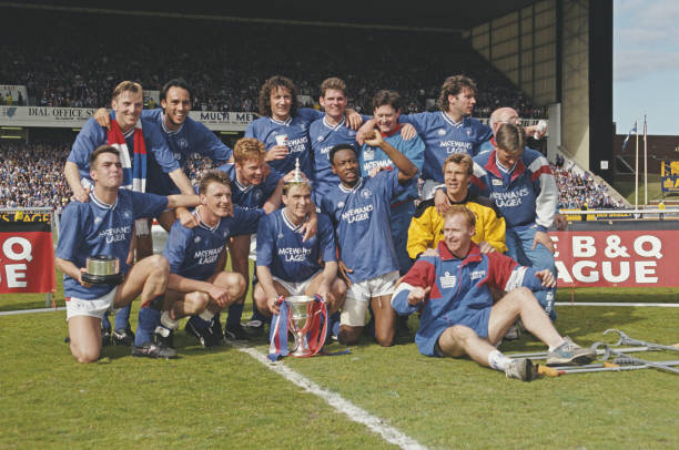 Members of the Rangers FC football team squad celebrate on the pitch with the trophy after beating Aberdeen 2-0 at Ibrox Stadium to win the 1990-91 Scottish Premier Division championship in Glasgow on 11th May 1991. Squad team members that played in the match include: Chris Woods, Gary Stevens, Scott Nisbet, John Brown, Ally McCoist, Tom Cowan, Ian Durrant, terry Hurlock, Nigel Spackman, Ian Ferguson, Mark Walters, Mark Hateley and Mo Johnston.