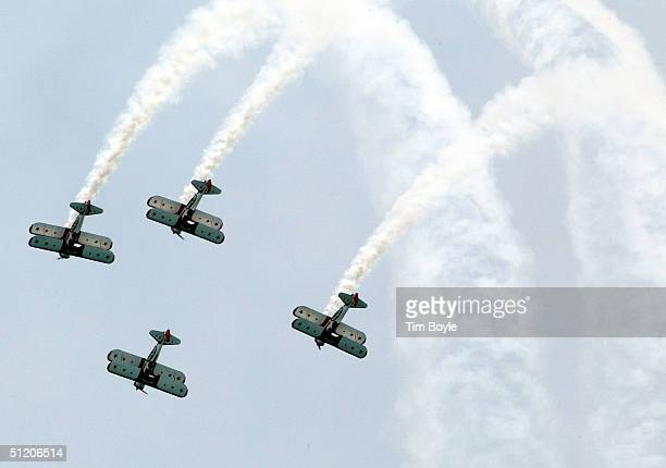 Members of the Red Baron Pizza Squadron do a maneuver as they fly over Lake Michigan August 22 2004 in Chicago Illinois The Red Baron Pizza Squadron...
