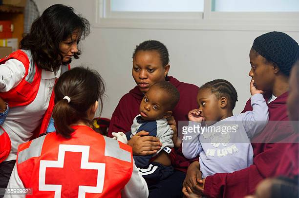 Members of the Red Cross tend to wouldbe immigrants and their children upon their arrival at Tarifa's port near Cadiz on November 10 2012 Spanish...