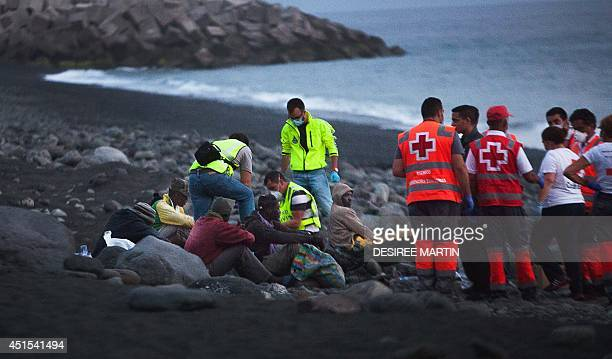 Members of the Red Cross tend to wouldbe immigrants upon their arrival in Tazacorte on the Spanish Canary Island of La Palma on June 30 2014 The 12...