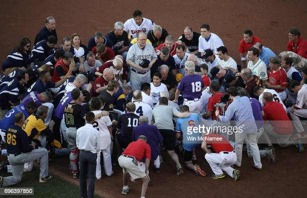 Members of the Republican and Democratic congressional baseball teams gather for a bipartisan prayer before the start of the Congressional Baseball...