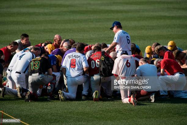 TOPSHOT Members of the Republican team say a prayer before the Congressional Baseball Game between Democrats and Republicans at Nationals Stadium...