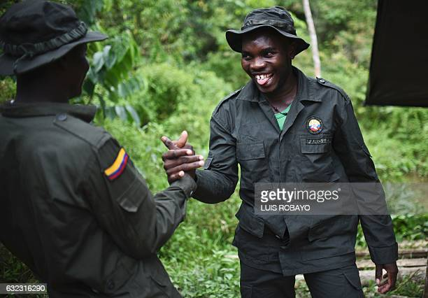 TOPSHOT Members of the Revolutionary Armed Forces of Colombia guerrilla smile at the Alfonso Artiaga Front 29 FARC encampment in a rural area of...