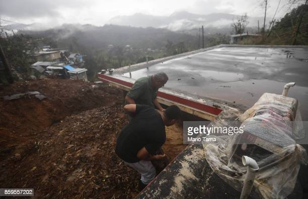 Members of the Reyes family stand atop a mudslide as they look beneath the roof of their home after Hurricane Maria hit the island on October 9 2017...