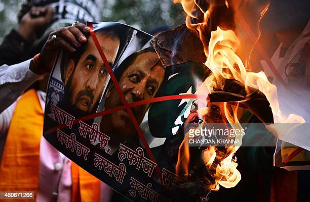 Members of the rightwing Hindu Sena burn a poster bearing images of Pakistani Prime Minister Nawaz Sharif and Hafiz Muhammad Saeed and ZakiurRehman...