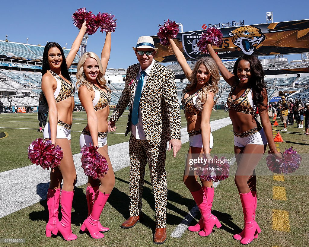 Members of the ROAR Cheerleaders of the Jacksonville Jaguars pose on the field with a fan who is dressed in a Jaguar printed suit before the game against the Oakland Raiders at EverBank Field on October 23, 2016 in Jacksonville, Florida. The Raiders defeated the Jaguars 33 to 16.