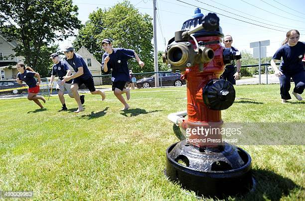 Members of the Rollinsford New Hampshire Fire Department take off at the start of the wet hose competition during the muster in York Sunday July 1...