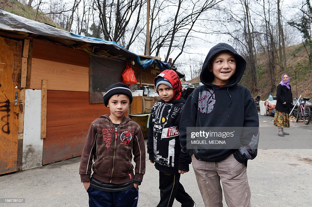 Members of the Roma community stand near their shanty houses on the periphery of Paris on December 26, 2012. AFP PHOTO / Miguel Medina
