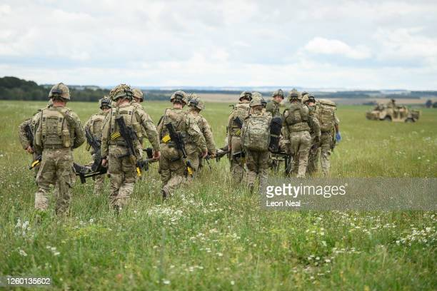 """Members of the Royal Army Medical Corp carry two """"injured"""" soldiers to a medical evacuation point during a military exercise on Salisbury Plains on..."""