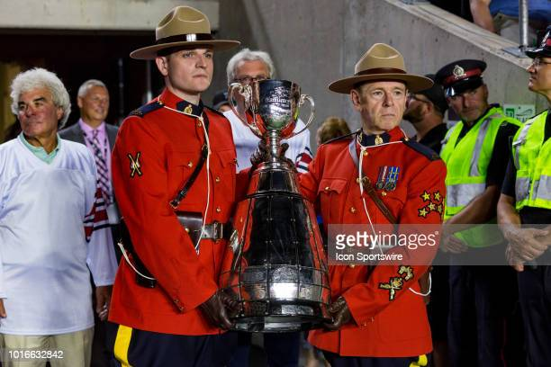 Members of the Royal Canadian Mounted Police hold the Grey Cup Trophy during Canadian Football League action between the Montreal Alouettes and...
