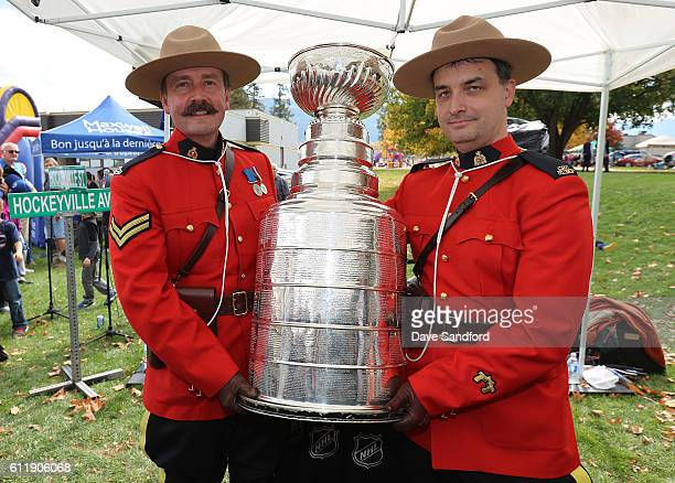 Members of the Royal Canadian Mounted Police hold the Stanley Cup at Oval Park during Day 2 of NHL Kraft Hockeyville Canada on October 1 2016 in...