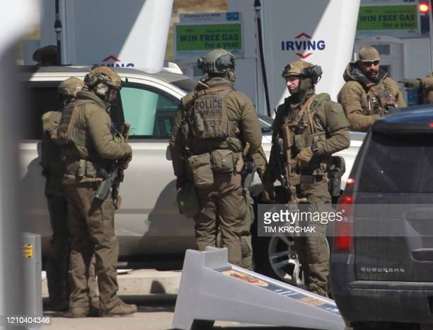 Members of the Royal Canadian Mounted Police tactical unit confer after the suspect in a deadly shooting rampage was neutralized at the Big Stop near...