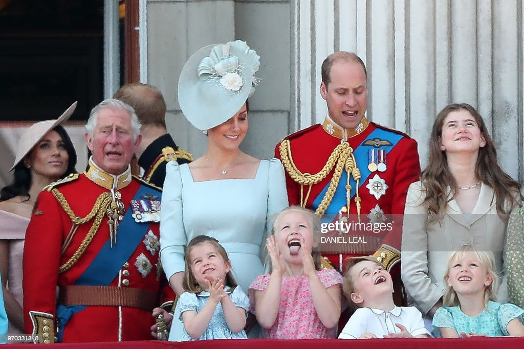 TOPSHOT - Members of the Royal Family (L-R) Britain's Meghan, Duchess of Sussex, Britain's Prince Charles, Prince of Wales, Britain's Catherine, Duchess of Cambridge (with Princess Charlotte and Prince George) and Britain's Prince William, Duke of Cambridge, stand on the balcony of Buckingham Palace to watch a fly-past of aircraft by the Royal Air Force, in London on June 9, 2018. - The ceremony of Trooping the Colour is believed to have first been performed during the reign of King Charles II. In 1748, it was decided that the parade would be used to mark the official birthday of the Sovereign. More than 600 guardsmen and cavalry make up the parade, a celebration of the Sovereign's official birthday, although the Queen's actual birthday is on 21 April.