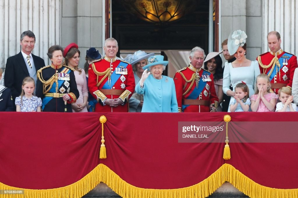 TOPSHOT - Members of the Royal Family (L-R) Vice Admiral Timothy Laurence, Britain's Princess Anne, Princess Royal, Britain's Princess Beatrice of York, Britain's Prince Andrew, Duke of York, Britain's Camilla, Duchess of Cornwall, Britain's Queen Elizabeth II, Britain's Prince Charles, Prince of Wales, Britain's Meghan, Duchess of Sussex, Britain's Prince Harry, Duke of Sussex, Britain's Catherine, Duchess of Cambridge (with Princess Charlotte and Prince George) and Britain's Prince William, Duke of Cambridge, stand on the balcony of Buckingham Palace to watch a fly-past of aircraft by the Royal Air Force, in London on June 9, 2018. - The ceremony of Trooping the Colour is believed to have first been performed during the reign of King Charles II. In 1748, it was decided that the parade would be used to mark the official birthday of the Sovereign. More than 600 guardsmen and cavalry make up the parade, a celebration of the Sovereign's official birthday, although the Queen's actual birthday is on 21 April.