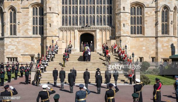 Members of the royal family watch as Prince Philip, Duke of Edinburgh's coffin, covered with His Royal Highness's Personal Standard arrives at St...