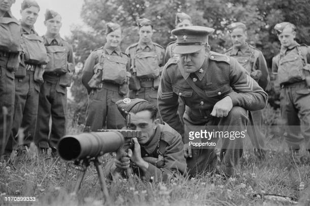 Members of the Royal Militia of the Island of Jersey a unit of the British Army receive instruction from a sergeant on the operation of a Lewis Gun...