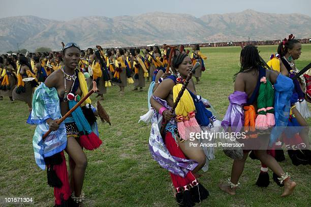 Members of the royal Swazi family dance with young girls dance at a traditional Reed dance ceremony at the stadium at the Royal Palace on August 30...