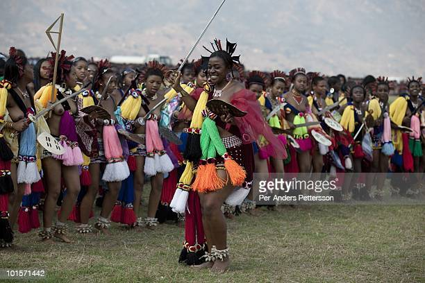 Members of the royal Swazi family dance with young girls dance at a traditional Reed dance ceremony at the stadium at the Royal Palace on August 31...