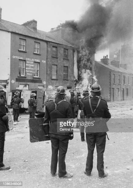Members of the Royal Ulster Constabulary look on as a building goes up in flames as violence flared between local residents, organised under the...