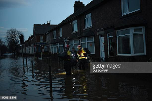 Members of the RSPCA help a woman retrieve possessions from her flooded property in Carlisle north west England on December 7 after heavy flooding...