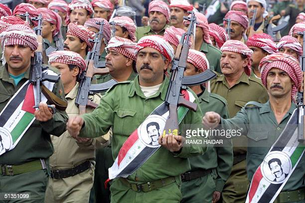 Members of the ruling Baath party parade with kalashnikovs and portraits of Iraqi President Saddam Hussein on Iraqi flags in Baghdad 08 February 2002...
