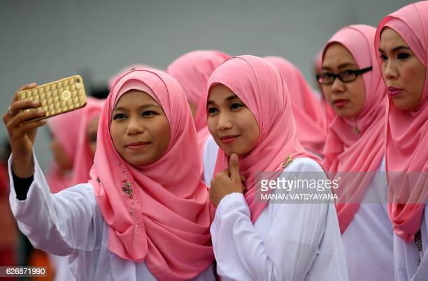 Members of the ruling party United Malays National Organisation pose for photographs before the opening ceremony of the party's annual congress in...