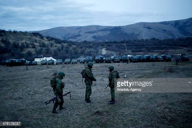 Members of the Russian armed forces stand guard around the Ukrainian military base in the village of Perevalne 20 km south of Simferopol on March 2...