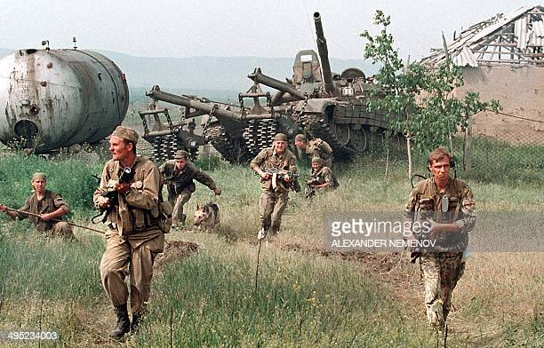 Members of the Russian Army 'special forces' followed by a tank enter in May 1996 in the Chechen stronghold of Bamut a village in western Chehnya...