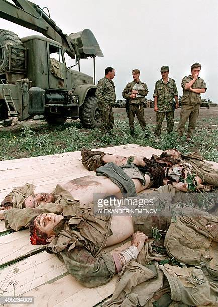 Members of the Russian Army 'special forces' look at the bodies of Chechen fighters in May 1996 in the Chechen stronghold of Bamut a village in...