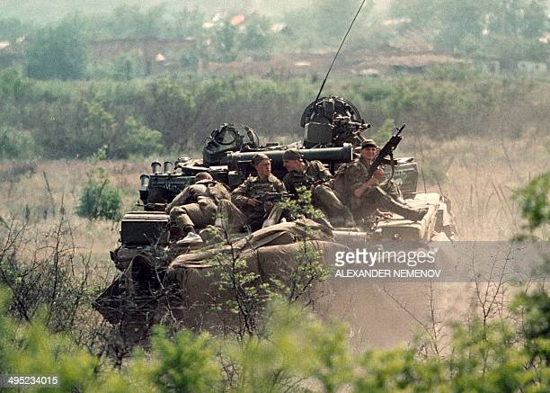 Members of the Russian Army 'special forces' sitting on top of a armoured personnel carrier enter 05 May 1996 in the Chechen stronghold of Bamut in...