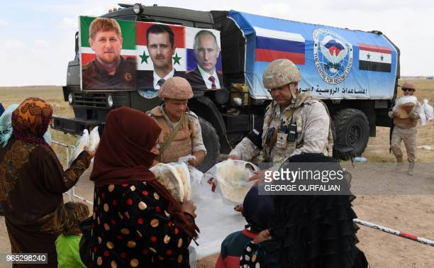Members of the Russian military police hand out food aid provided by a Chechen charity to Syrians queueing up after arriving in a convoy returning...