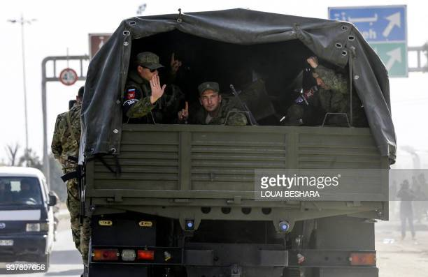 Members of the Russian military police ride in the back of an truck on the outskirts of the capital Damascus near the entrance of Harasta in the...
