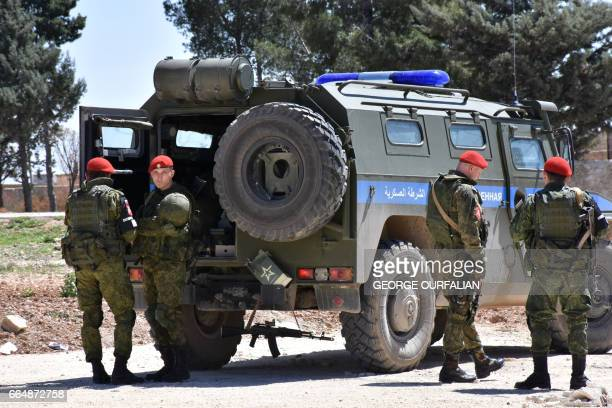 Members of the Russian Military police stand guard in the northern city of Manbij as Syrians who fled the city of Aleppo due to the fighting prepare...