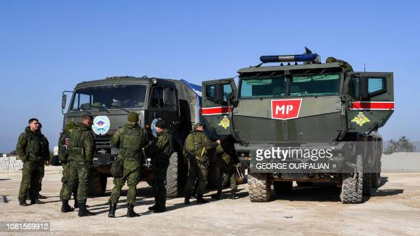 Members of the Russian military police stand outside armoured troop transports in the village of Arima west of the northern Syrian town of Manbij on...