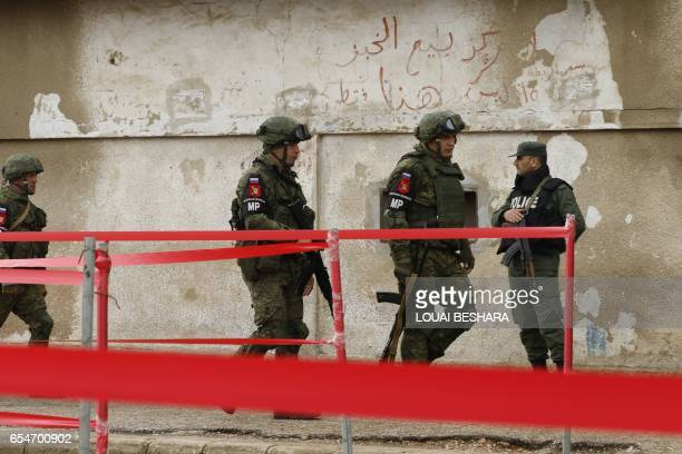 Members of the Russian Military police walk past a Syrian regime soldier during the first phase of the Russiansupervised deal to complete the...