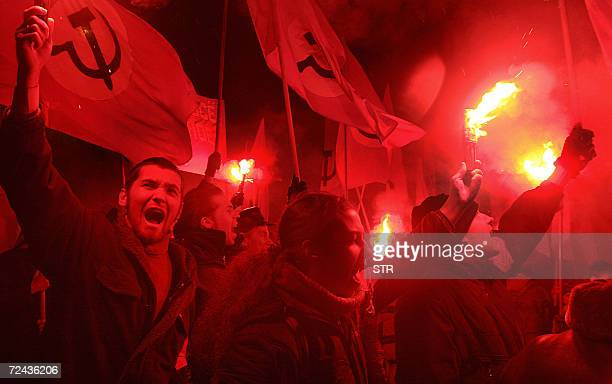 Members of the Russian nationalbolshevik party shout slogans and carry flares during a rally commemorating the anniversary of the Great October...