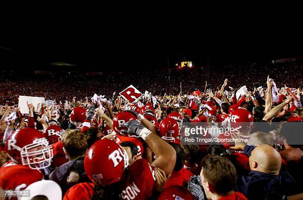 Members of the Rutgers Scarlet Knights Football Team and their fans rush the field after defeating the Louisville Cardinals at Rutgers Stadium on...